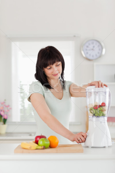 Bonitinho morena feminino batedeira em pé cozinha Foto stock © wavebreak_media