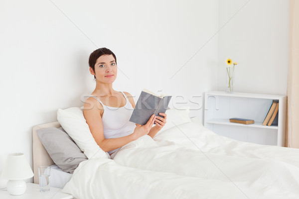 Stock photo: Young woman reading a book in her bedroom