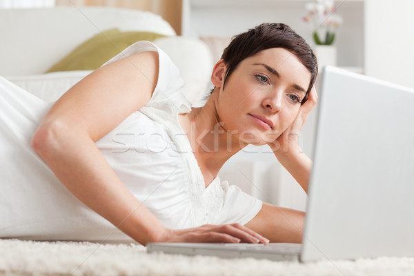 Close up of a serious woman relaxing with a laptop while lying on her carpet Stock photo © wavebreak_media