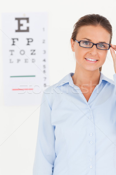 Stock photo: Good looking brunette eye specialist wearing glasses looking into the camera in her surgery