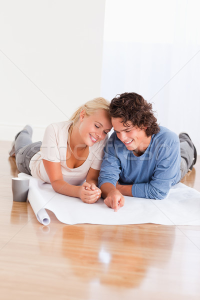 Portrait of a young couple organizing their new home while lying on the floor Stock photo © wavebreak_media