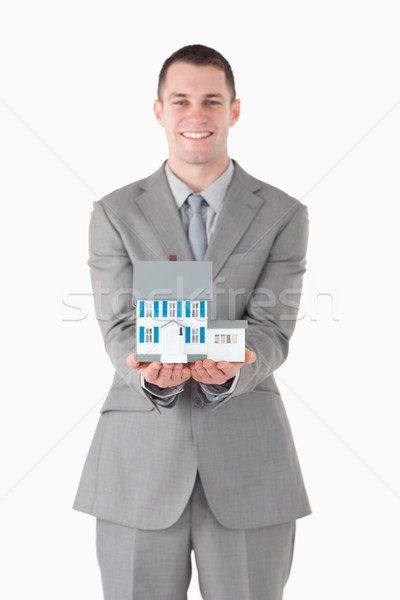 Portrait of a businessman holding a miniature house against a white background Stock photo © wavebreak_media