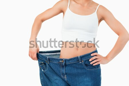 Thin woman wearing too large jeans against a white background Stock photo © wavebreak_media