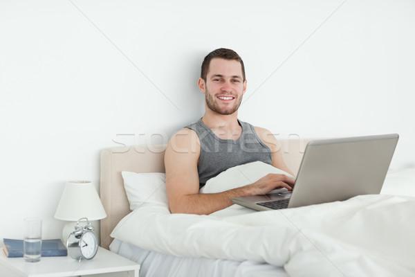 безмятежный человека используя ноутбук спальня компьютер счастливым Сток-фото © wavebreak_media