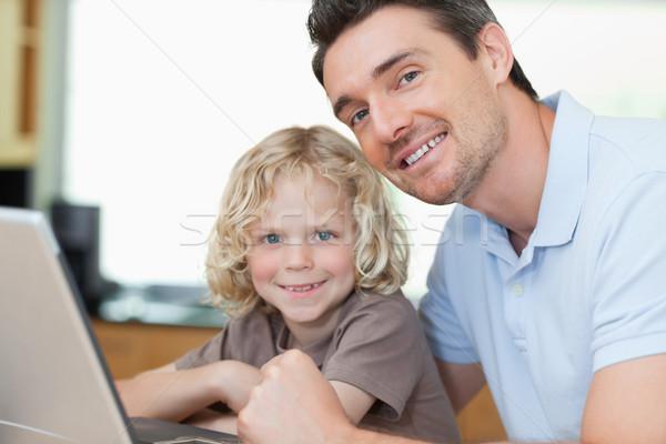 Uśmiechnięty syn ojca wraz notebooka rodziny dziecko Zdjęcia stock © wavebreak_media