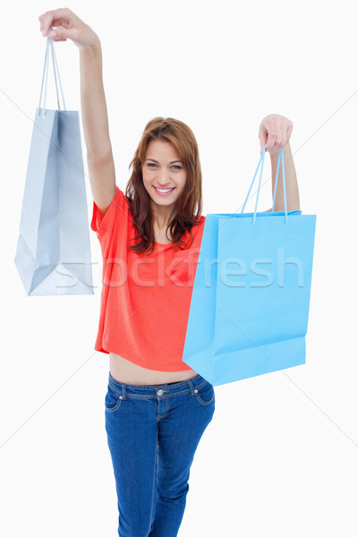 Teenage raising her shopping bags in the air while smiling Stock photo © wavebreak_media