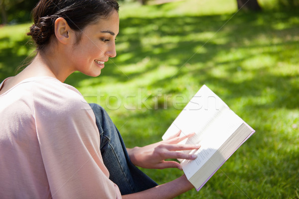 Woman smiling while reading a book as she sits sits in the grass Stock photo © wavebreak_media