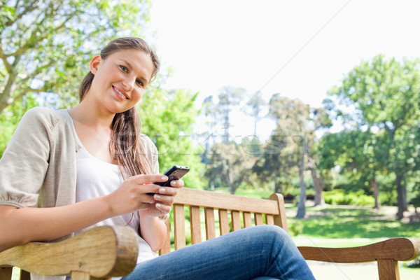 Smiling young woman writing a text message on a park bench Stock photo © wavebreak_media