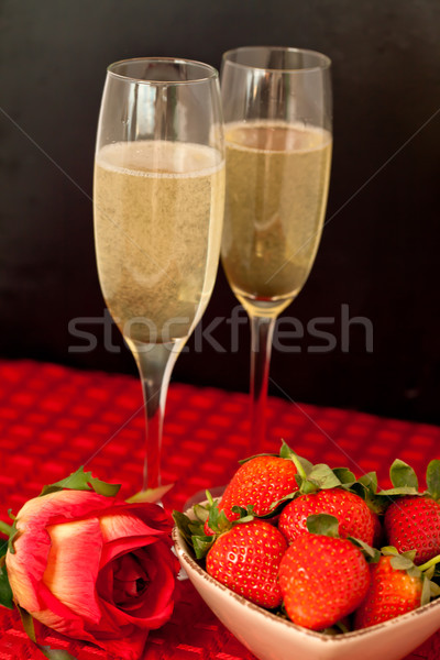 Top glasses of champagne with strawberries in a bowl and a rose on a red tablecloth against a black  Stock photo © wavebreak_media