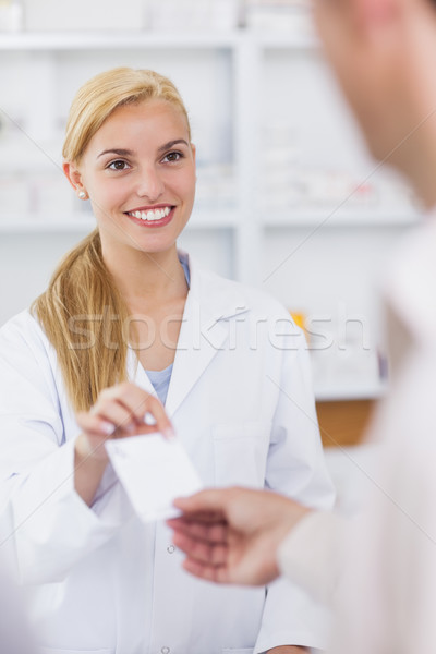Patient giving a prescription to a smiling pharmacist in hospital  Stock photo © wavebreak_media