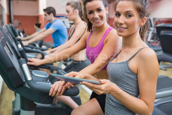 Instructor and woman smiling in the gym on the exercise bicycle Stock photo © wavebreak_media