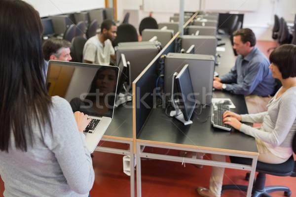 Computer class working as teacher is typing on laptop in college Stock photo © wavebreak_media