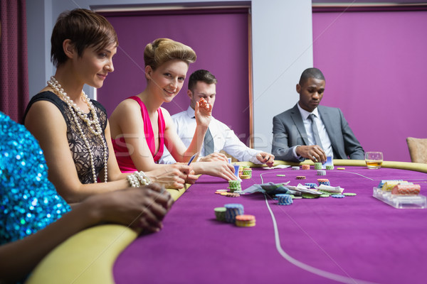 Stock photo: People sitting at the casino table and smiling