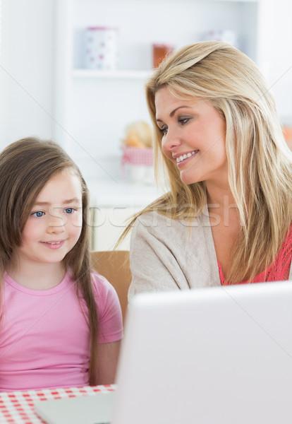 Photo stock: Mère · souriant · fille · utilisant · un · ordinateur · portable · cuisine · femme