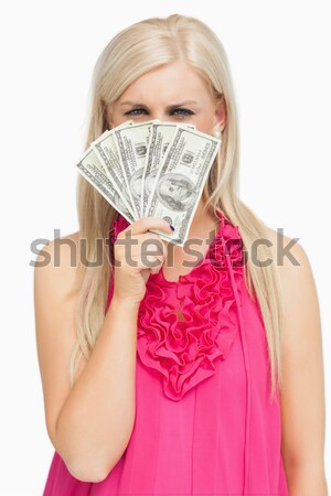 Woman holding fanned banknotes in front of face with eyes closed Stock photo © wavebreak_media