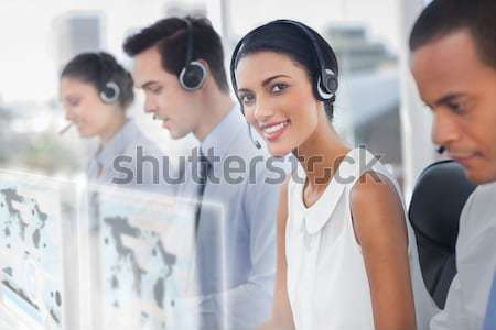 Smiling call center employees sitting in line Stock photo © wavebreak_media