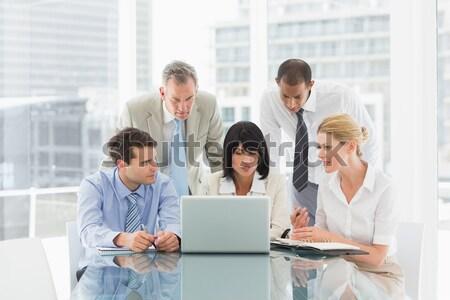 Gelukkig zakenlieden rond laptop naar camera Stockfoto © wavebreak_media