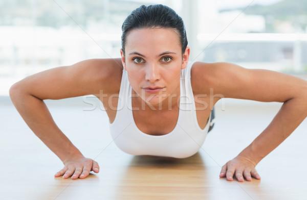 Determined beautiful woman doing push ups in gym Stock photo © wavebreak_media
