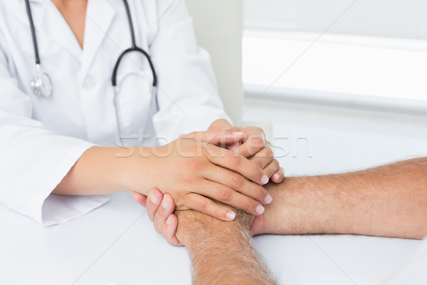 Close-up mid section of a doctor holding patients hands Stock photo © wavebreak_media