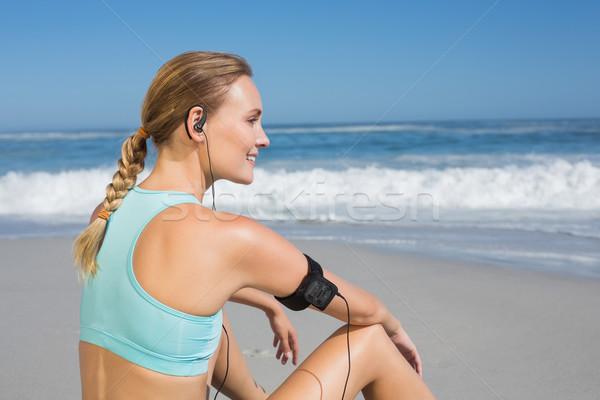 Fit woman sitting on the beach taking a break smiling  Stock photo © wavebreak_media