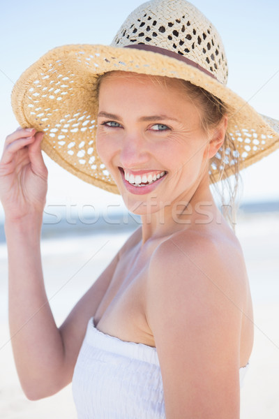 Pretty smiling blonde on the beach wearing straw hat Stock photo © wavebreak_media