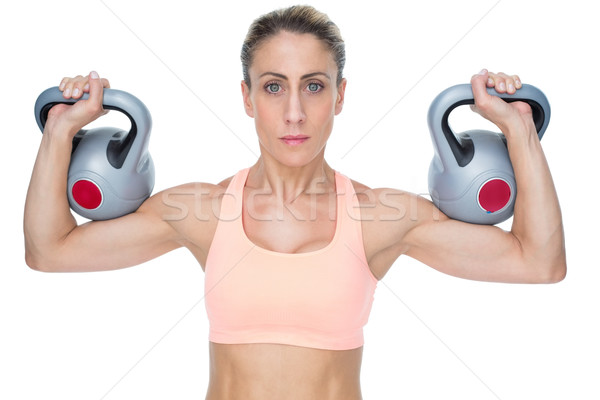 Serious female crossfitter lifting kettlebells looking at camera Stock photo © wavebreak_media
