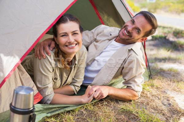 Outdoorsy couple smiling at camera inside their tent Stock photo © wavebreak_media