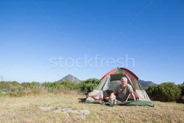 Happy camper cooking on camping stove outside his tent Stock photo © wavebreak_media