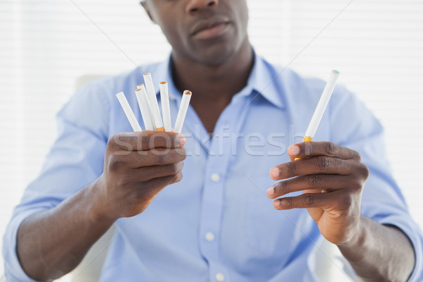 Businessman deciding between electronic or normal cigarettes Stock photo © wavebreak_media