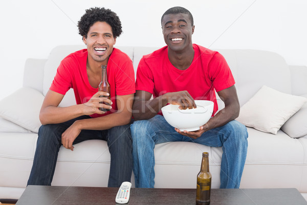 Futebol fãs vermelho sessão sofá cerveja Foto stock © wavebreak_media