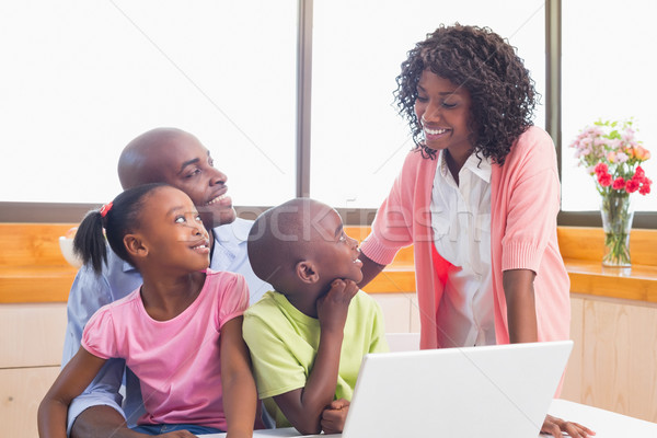 Cute siblings using laptop together with parents Stock photo © wavebreak_media