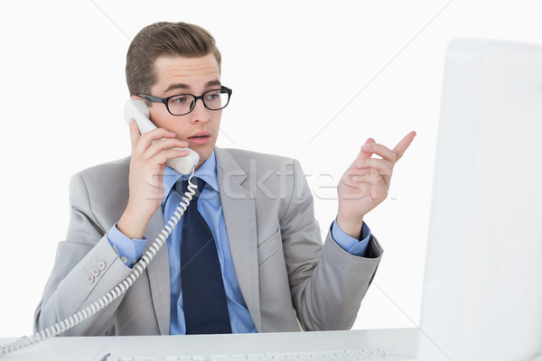Stock photo: Nerdy businessman working on computer talking on phone
