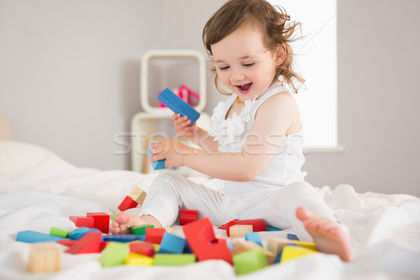 Cute girl playing with building blocks on bed Stock photo © wavebreak_media