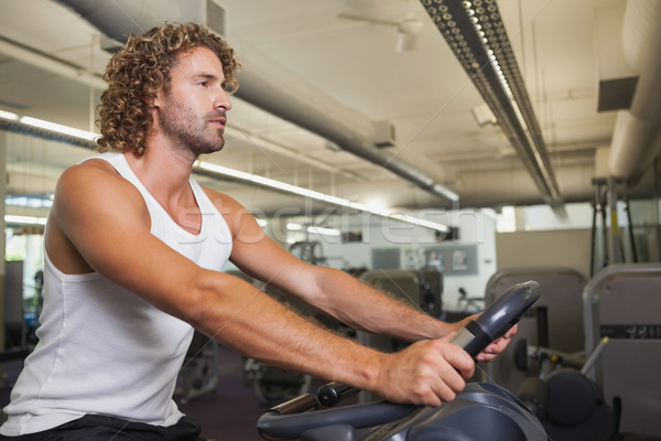 Side view of man working out on exercise bike at gym Stock photo © wavebreak_media