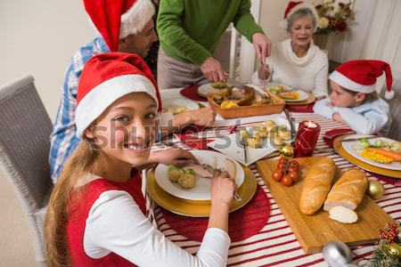 Smiling extended family in party hat at dinner table Stock photo © wavebreak_media