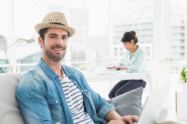 Lächelnd Geschäftsmann eingeben Laptop Couch Kollege Stock foto © wavebreak_media