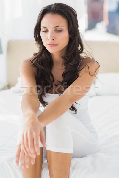 Anxieux brunette séance lit maison chambre Photo stock © wavebreak_media
