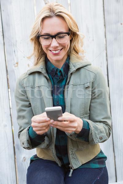 Boldog szőke nő szemüveg sms üzenetküldés fából készült deszkák Stock fotó © wavebreak_media