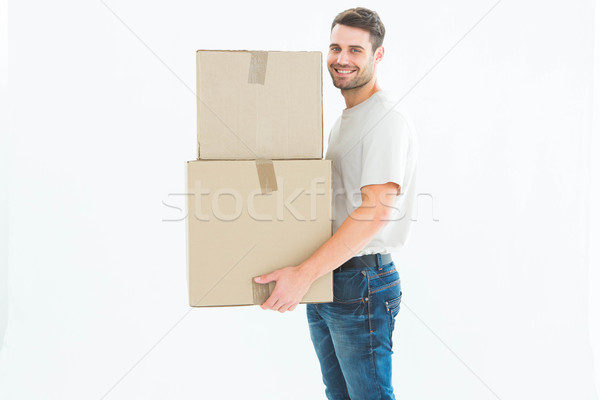 Happy delivery man carrying cardboard boxes Stock photo © wavebreak_media