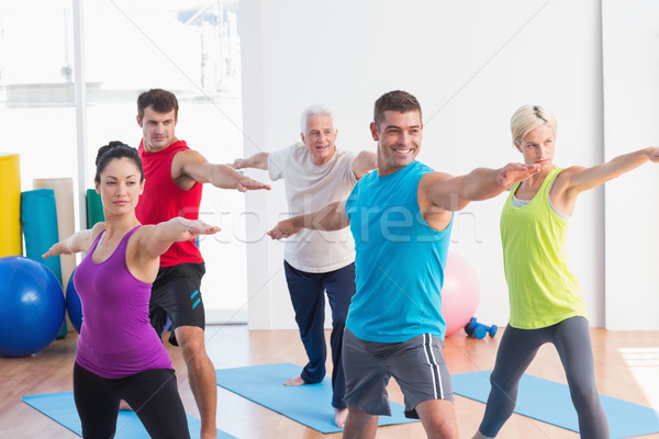 People doing warrior pose in yoga class Stock photo © wavebreak_media