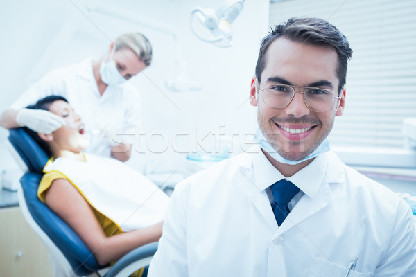 Smiling male dentist with assistant examining womans teeth Stock photo © wavebreak_media