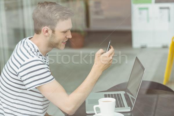 Zdjęcia stock: Uśmiechnięty · student · za · pomocą · laptopa · smartphone · Kafejka · uczelni