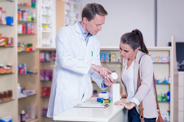 Gyógyszerész mutat drog doboz fiatal nő gyógyszertár Stock fotó © wavebreak_media