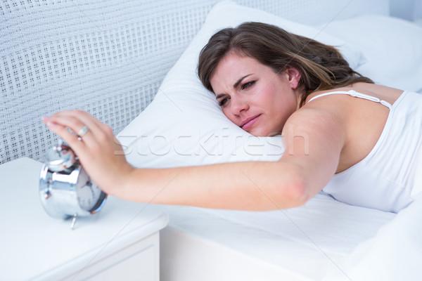 Güzel kadın el çalar saat yatak ev yatak odası Stok fotoğraf © wavebreak_media
