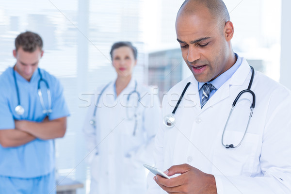 Attentive doctor sending a text message Stock photo © wavebreak_media