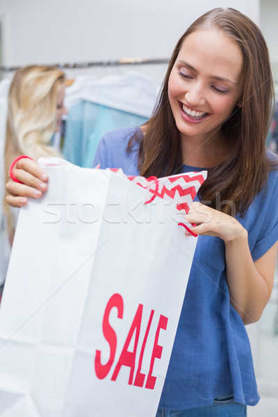Pretty brunette opening a discounted bag Stock photo © wavebreak_media