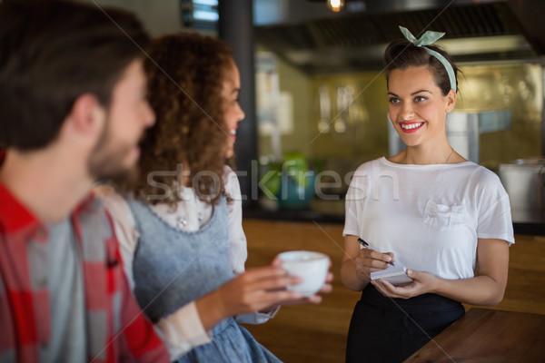 Sonriendo camarera toma restaurante clientes hombre Foto stock © wavebreak_media