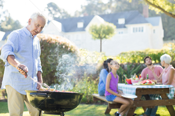 Senior man preparing barbecue while family having meal Stock photo © wavebreak_media