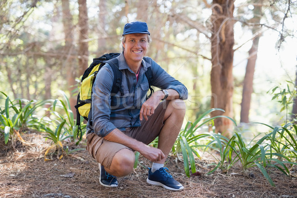 Portrait of hiker kneeling on trail against trees Stock photo © wavebreak_media