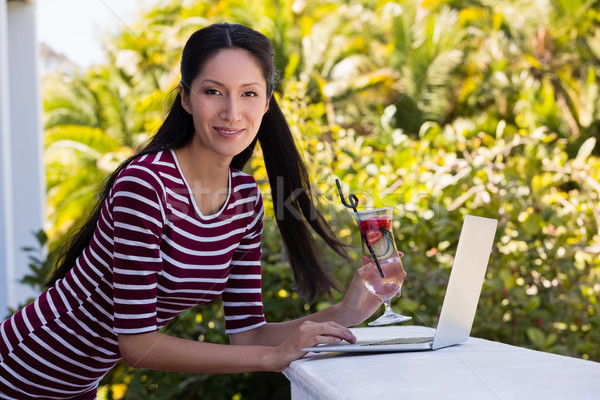 Woman holding cocktail drink while using laptop on retaining wall Stock photo © wavebreak_media